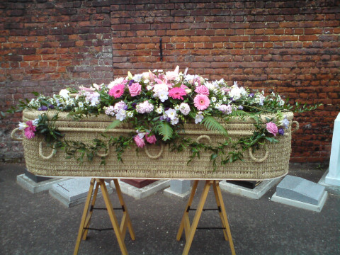 Wicker eco coffin with flower garland